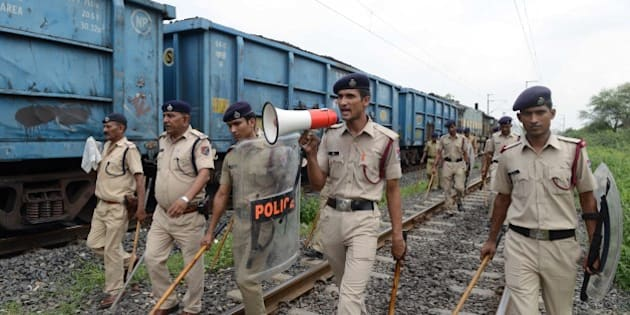 Indian police patrol railway tracks damaged by rioters on the outskirts of Ahmedabad on August 26, 2015.  Thousands of Indian paramilitary troops have been sent to the western state of Gujarat to contain violence that broke out after an estimated half a million of the Patidar or Patel caste rallied to demand favourable treatment. Authorities have imposed a curfew in parts of Ahmedabad and five other cities and towns after stone-throwing members torched cars, buses and police stations.  AFP PHOTO / Sam PANTHAKY        (Photo credit should read SAM PANTHAKY/AFP/Getty Images)