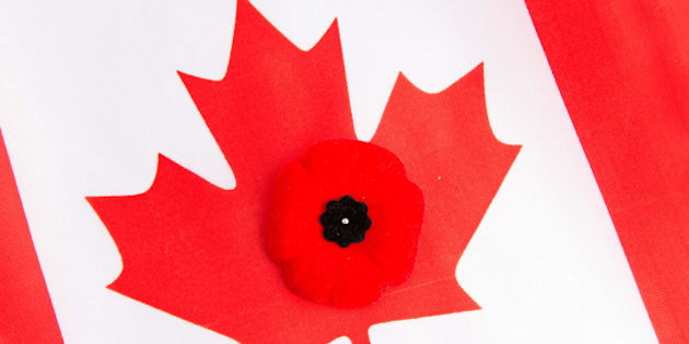 TORONTO, ONTARIO, CANADA - 2013/11/14: Canadian flag and a red poppy. The red poppy is the Canadian sign of remembering our veterans. Worn on the left side close to the heart, the poppy has become a symbol of Remembrance Day in Canada. (Photo by Roberto Machado Noa/LightRocket via Getty Images)