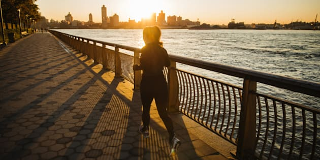 Woman jogging along the East River in Manhattan, New York, United States, North America.