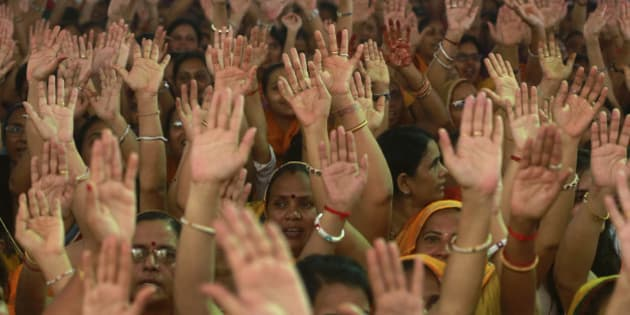 Members of Jain community raise their hands as they shout slogans  during a protest in Mumbai, India, Monday, Aug. 24, 2015. The protest was against the recent Rajasthan High Court order of banning the religious practice of Santhara, a practice of fasting unto death. (AP Photo/Rafiq Maqbool)