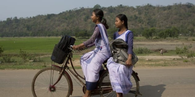 Indian girls go to a school on a bicycle at Roja Mayong village about 40 kilometers (25 miles) east of Gauhati, India, Thursday, April 9, 2015. According to the UNESCO Education for All Global Monitoring Report 2015, only half of all countries have achieved the most watched goal of universal primary enrollment. The report launched Thursday says, India has reduced its out of school children by over 90% Since 2000. (AP Photo/ Anupam Nath)