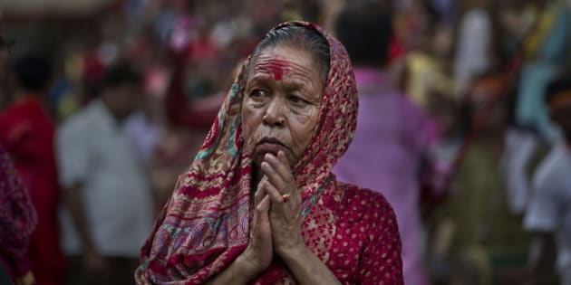 An Indian devotee offers prayers as she watches a priest carry a goat for sacrifice during the Deodhani festival at the Kamakhya Hindu temple in Gauhati, India, Wednesday, Aug. 19, 2015. During this festival devotees sacrifice goats and pigeons. (AP Photo/ Anupam Nath)