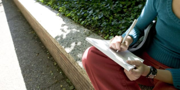 Woman writing in park