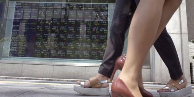 Women walk past an electronic stock indicator of a securities firm showing Tokyo's Nikkei 225 in Tokyo, Wednesday, June 24, 2015. (AP Photo/Shuji Kajiyama)