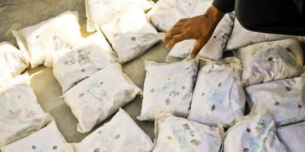 """A member of the Counter Narcotics Police of Afghanistan (CNPA) in Lashkar Gah, Helmand Province, Afghanistan, showing seized heroin. Each bag contains £70,000 (street value) worth of heroin rocks.  Imagery captured showing the work of the Provincial Reconstruction Team (PRT) in central Helmand Province, Afghanistan. The Helmand PRT is a mulitnational team, with staff supplied by the UK, US, Danish and Estonian governments.   The UK has run the management platform for the PRT since 1 May 2006, when it assumed responsibility from the US.   The PRT comprises 91 civilian, 94 military and 27 civilian police staff in Lashkar Gah and district centres across Helmand.  It also employs approximately 30 locally engaged staff, bringing the total staff to 242. The PRT helps the Afghan Government deliver effective government and security across all Helmand Province.Photographer: SAC Neil Chapman (RAF) Image 45152423.jpg from <a href=""""http://www.defenceimages.mod.uk"""" rel=""""nofollow"""">www.defenceimages.mod.uk</a>  For latest news visit: <a href=""""http://www.mod.uk"""" rel=""""nofollow"""">www.mod.uk</a> Follow us: <a href=""""http://www.facebook.com/defenceimages"""" rel=""""nofollow"""">www.facebook.com/defenceimages</a> <a href=""""http://www.twitter.com/defenceimages"""" rel=""""nofollow"""">www.twitter.com/defenceimages</a>"""