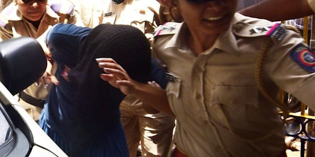 This photo taken on August 29, 2015 shows former Indian media executive Indrani Mukherjea being escorted into a police station through a scrum of media in Mumbai. A former Indian media executive has been arrested on suspicion of murdering her daughter for having an affair with her stepson, Mumbai police said August 27, in a case gripping India. Indrani Mukerjea is accused, along with two others, of strangling Sheena Bora to death in 2012 before dumping her body in a forest in western Maharashtra state and setting it alight. AFP PHOTO        (Photo credit should read STR/AFP/Getty Images)