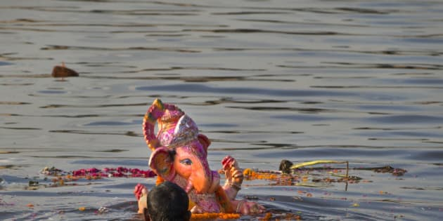 An Indian Hindu devotee immerses an idol of the elephant-headed Hindu God Ganesh into the river Yamuna, in New Delhi, India, Monday, Sept. 8, 2014. Every year millions of devout Hindus immerse Ganesh idols into oceans and rivers in the ten-day long Ganesh Chaturthi festival that celebrates the birth of Ganesh. (AP Photo /Manish Swarup)