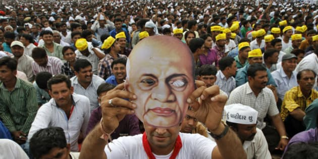 A Patidar or member of Patel community holds a mask of Indian freedom fighter and first Home Minister of Independent India Sardar Vallabhbhai Patel as he participates in a rally in Ahmadabad, India, Tuesday, Aug. 25, 2015. Members of Patel community held a rally Tuesday demanding reservations under the Other Backward Class (OBC) quota. (AP Photo/Ajit Solanki)
