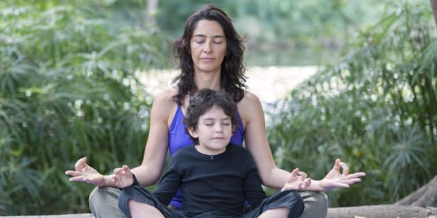 Hispanic mother and son practicing yoga