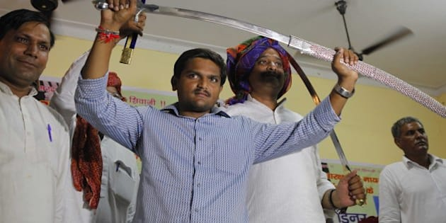 NEW DELHI, INDIA - AUGUST 30: Hardik Patel, Convener of Patidar Anamat Andolan Samiti (PAAS) being felicitated by Gurjar Community at Kotla Village, Gurjar Bhawan near Patparganj, on August 30, 2015 in New Delhi, India. Patel announced that he won't allow any political party to join his agitation and he wants to turn the stir into a national movement. He strongly defended his demand for reservation for Patels or Patidars, saying they are not getting jobs due to reservation. He said, 'We are not here to meet any ministers. Political parties are not welcome in the agitation.' (Photo by Arvind Yadav/Hindustan Times via Getty Images)