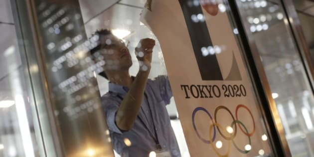 The poster with a logo of Tokyo Olympic Games 2020 is removed from the wall by a worker during an event staged for photographers at the Tokyo Metropolitan Government building in Tokyo Tuesday, Sept. 1, 2015.  Tokyo Olympic organizers on Tuesday decided to scrap the logo for the 2020 Games following another allegation its Japanese designer might have used copied materials.(AP Photo/Eugene Hoshiko)