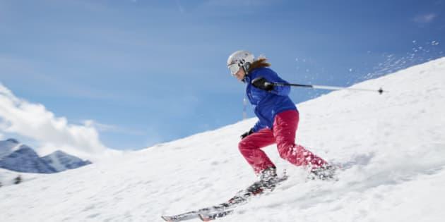 Young woman skiing down mountain
