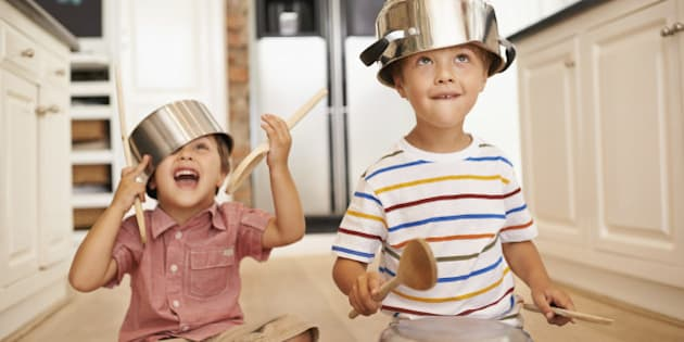 Two young boys sitting on the kitchen floor playing with pots and pans
