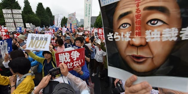 People shout slogans as they hold banners during an anti-government rally in front of the National Diet in Tokyo on August 30, 2015 to protest against Japan's Prime Minister Shinzo Abe's controversial security bills which would expand the remit of the country's armed forces.  Tens of thousands of people took part in the rallies held around the Diet.  AFP PHOTO / Toru YAMANAKA        (Photo credit should read TORU YAMANAKA/AFP/Getty Images)