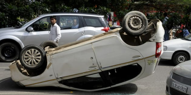 GURGAON, INDIA - JULY 15: An Etios car turned over after accident with the Hyundai SUV car after it was shot at by unidentified persons at MG Road on July 15, 2015 in Gurgaon, India. Unidentified persons in a black Santro fired at gangster Rakesh Yadav who was driving white Hyundai SUV, which jumped the road divider and fell on the auto-rickshaw, killing its driver. Yadav, who has over one dozen criminal cases registered against him, is the main accused in the killing of Hayatpur sarpanch (village head) Rakesh Kumar Yadav. (Photo by Parveen Kumar/Hindustan Times via Getty Images)