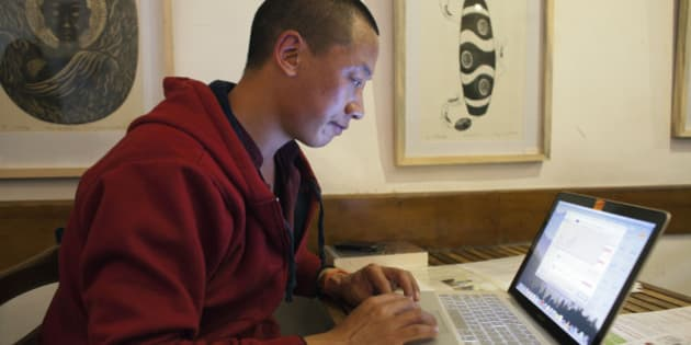 Jamyang Palden, a 30-year-old Tibetan Buddhist monk uses his laptop to access his email at a cafe with WiFi connection in Dharmsala, India, Monday, Nov. 10, 2014. Buffeted by constant cyberattacks, monks like Palden are being taught a new Information Age creed: 'Detach from Attachments.' The Internet safety slogan is an example of how human rights defenders are seeking creative ways to protect activists from electronic espionage. (AP Photo/Ashwini Bhatia)