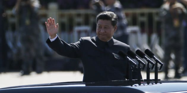 Chinese President Xi Jinping stands in a car and waves during a troop review during a parade commemorating the 70th anniversary of Japan's surrender during World War II held in front of Tiananmen Gate in Beijing, Thursday, Sept. 3, 2015.The spectacle involved more than 12,000 troops, 500 pieces of military hardware and 200 aircraft of various types, representing what military officials say is the Chinese military's most cutting-edge technology. (AP Photo/Ng Han Guan)