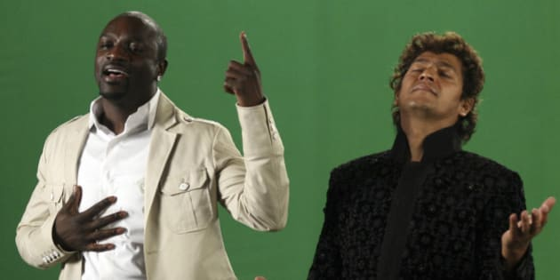 US singer Akon (L) performs with Indian music director Aadesh Shrivastava during a music video filming for the English-Hindi album 'One for the World' in Mumbai on December 8, 2010. AFP PHOTO/STR (Photo credit should read STRDEL/AFP/Getty Images)