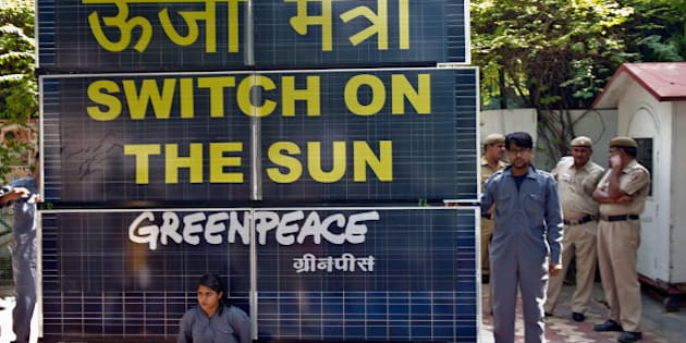Indian policemen look on as Greenpeace activists chained to a bank of solar panels block the entry to the residence of Delhi's Power Minister Haroon Yusuf in New Delhi on May 15, 2013. Greenpeace activists demanded that Delhi Government should take steps to improve its performance on the use of renewable source of energy to deal with capital's power crisis.   AFP PHOTO/Prakash SINGH        (Photo credit should read PRAKASH SINGH/AFP/Getty Images)
