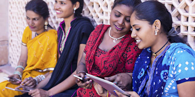 Indian women having sharing and talking with their digital devices.