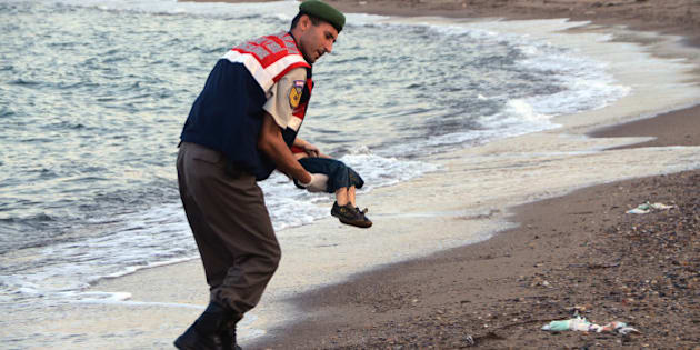 ADDS IDENTIFICATION OF CHILD   A paramilitary police officer carries the lifeless body of Aylan Kurdi, 3, after a number of migrants died and a smaller number were reported missing after boats carrying them to the Greek island of Kos capsized, near the Turkish resort of Bodrum early Wednesday, Sept. 2, 2015. The family — Abdullah, his wife Rehan and their two boys, 3-year-old Aylan and 5-year-old Galip — embarked on the perilous boat journey only after their bid to move to Canada was rejected. The tides also washed up the bodies of Rehan and Galip on Turkey's Bodrum peninsula Wednesday, Abdullah survived the tragedy. (AP Photo/DHA) TURKEY OUT