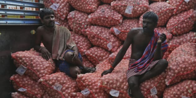 Indian workers rest on onion bags while loading them into a truck at a wholesale market in Hyderabad, India, Tuesday, Aug.25, 2015. The prices of onion, a staple food of the Indian middle class, have been soaring in the past weeks leading to protests. (AP Photo/Mahesh Kumar A.)