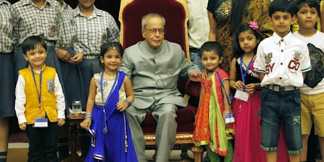 NEW DELHI, INDIA - AUGUST 29: President of India Pranab Mukherjee meeting the children on the auspicious occasion of Raksha Bandhan at Rashtrapati Bhavan on August 29, 2015 in New Delhi, India. On Raksha Bandhan, sisters tie a rakhi (sacred thread) on her brother's wrist, which symbolizes the sister's love and prayers for her brother's well-being and the brother's lifelong vow to protect her. (Photo by Raj K Raj/Hindustan Times via Getty Images)