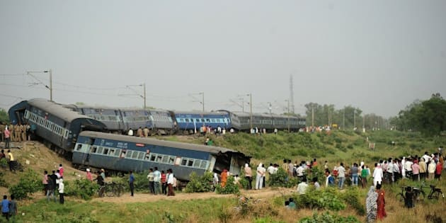 Indian bystanders look at the coaches of the derailed Muri Express train near Sirathu some 65kms from Allahabad on May 25, 2015. Two passengers have been killed after seven coaches of the Muri Express derailed near Sirathu in the northern state of Uttar Pradesh. AFP PHOTO/SANJAY KANOJIA        (Photo credit should read Sanjay Kanojia/AFP/Getty Images)