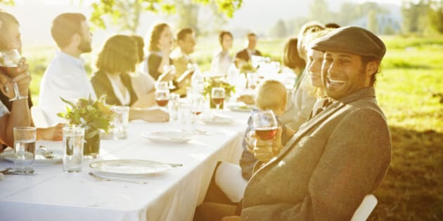 Man sitting at end of banquet table outside in field laughing holding glass of wine