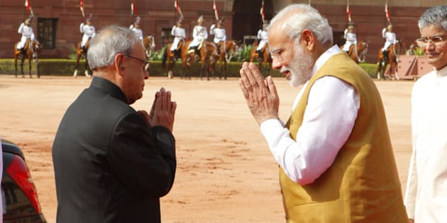 NEW DELHI, INDIA - AUGUST 26: Prime Minister Narendra Modi and President Pranab Mukherjee greet each other during the ceremonial reception of Seychelles President James Alix Michel at Rashtrapati Bhavan on August 26, 2015 in New Delhi, India. India and Seychelles on Wednesday exchanged five documents, including one on exchanging tax information and a Memorandum of Understanding (MoU) for providing a Dornier maritime surveillance aircraft. (Photo by Arvind Yadav/Hindustan Times via Getty Images)