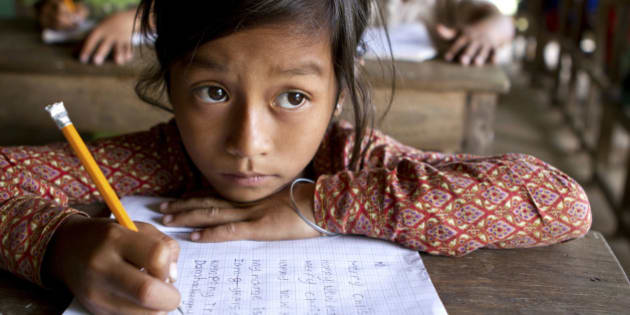 A young Asian girl studies hard her English writing skills (look at what she's writing down).