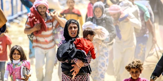 SANLIURFA, TURKEY - JUNE 16: Syrians fleeing the clashes in the city of Tal Abyad, cross into Turkey from the borderline in Akcakale district of Sanliurfa on June 16, 2015. Hundreds of Syrians who fled from Syria after clashes in the city of Tal Abyad, which borders Turkey, have crossed into Turkey since the beginning of June. (Photo by Ali hsan Ozturk/Anadolu Agency/Getty Images)