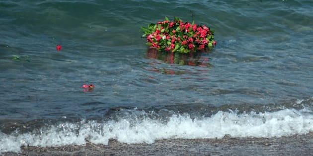 MUGLA, TURKEY - SEPTEMBER 4: Flowers are seen in the sea as people commemorate Aylan Kurdi, the three-year-old boy dressed in shorts and a red T-shirt, and 12 Syrians who drowned in the Aegean Sea after two boats filled with refugees en route to Greece sank, at the beach where they washed ashore in Mugla, Turkey on September 4, 2015. (Photo by Mustafa Ciftci/Anadolu Agency/Getty Images)