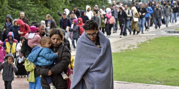 Migrants walk from the main station in Dortmund, Germany, to a hall where they get first attendance Sunday, Sept. 6, 2015. Thousands of migrants and refugees arrived in Dortmund by trains. (AP Photo/Martin Meissner)