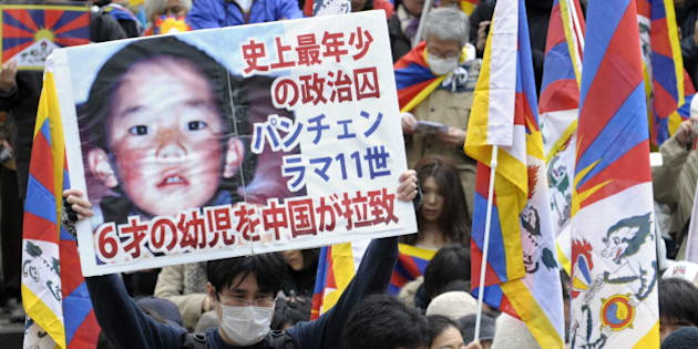 A protester holds a placard with portrait of Dalai Lama's choice for Panchen Lama, Gedhun Choekyi Nyima (top) during a peace march in Tokyo on March 14, 2009 to mark the 50th anniversary of Tibetan uprising against Chinese rule.  Premier Wen Jiabao said on March 13, Tibet was prospering under Chinese rule, as he hit back at the Dalai Lama who this week said his Himalayan homeland had turned into 'hell on earth'.  AFP PHOTO / TOSHIFUMI KITAMURA (Photo credit should read TOSHIFUMI KITAMURA/AFP/Getty Images)