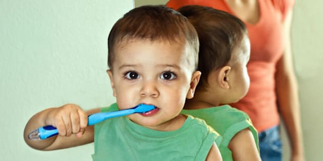 Hispanic toddler boy brushing teeth in bathroom.