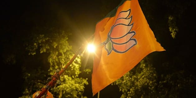 Indian Bharatiya Janata Party (BJP) supporters hold up a flag with the lotus party symbol outside the party headquarters in New Delhi on May 16, 2014. India's triumphant Hindu nationalists declared 'the start of a new era' in the world's biggest democracy May 16 after hardline leader Narendra Modi propelled them to a stunning win on a platform of revitalizing the sickly economy. AFP PHOTO/ SAJJAD HUSSAIN        (Photo credit should read SAJJAD HUSSAIN/AFP/Getty Images)