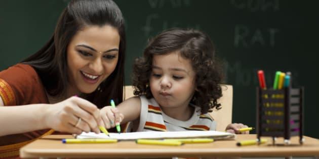 Teacher and schoolgirl (2-3) at desk