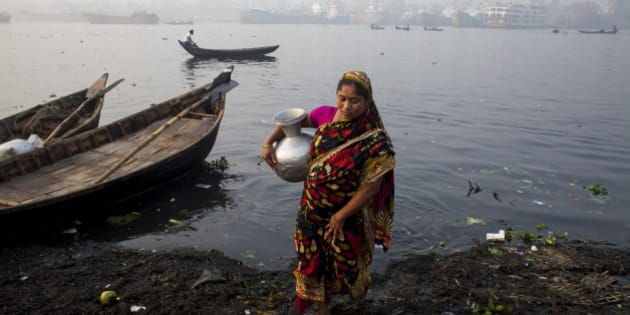 Women collected polluted water from Buriganga river for their daily needs, on February 23, 2015. A large swathe of the Buriganga River which is the lifeline of the capital has turned pitch-black with toxic waste, oil and chemicals flowing into it from industrial units. The water became extremely polluted and represents a health hazard for the riverbed communities