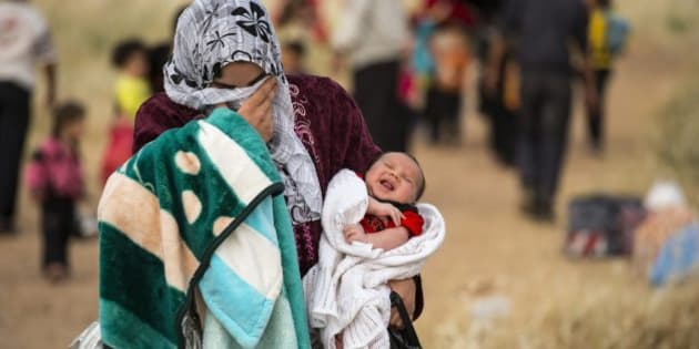 "A young mother crosses the border from Syria and becomes a refugee. She carries her one-month-old son, Hamid. ""Since he was born there has been non-stop bombing every day."" 