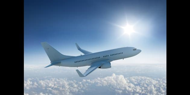 Airplane flies in blue sky above the clouds past the sun.