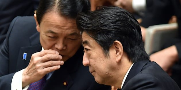 Japanese Minister Shinzo Abe (R) chats with Finance Minister Taro Aso (L) during a budget committee session of the House of Representatives at Parliament in Tokyo on February 25, 2015. Japan's farm minister resigned on February 23 after being accused of accepting illegal political funds, in a first blow to Prime Minister Shinzo Abe's new cabinet.    AFP PHOTO / KAZUHIRO NOGI        (Photo credit should read KAZUHIRO NOGI/AFP/Getty Images)