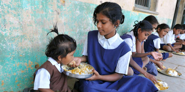 An Indian schoolgirl feeds her younger sister during their mid-day meal at a government primary school in the outskirts of Hyderabad on June 13, 2011, on the opening day of the new academic year. The government of India's Andhra Pradesh state has introduced English as a second language from Class 1 onwards for the 2011-2012 academic year. India's National Knowledge Commission has admitted that no more than one percent of country's population uses English as a second language. AFP PHOTO/Noah SEELAM (Photo credit should read NOAH SEELAM/AFP/Getty Images)