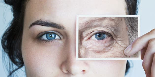 Young woman with photo of aged eye over her own
