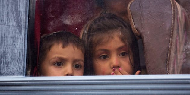 BICSKE, HUNGARY - SEPTEMBER 04:  Two migrant children look out of the window of a bus as migrants are escorted from a train by police after deciding to leave for fear of being taken to a refugee camp from the train which was held at Bicske station for two days on September 4, 2015 in Bicske, near Budapest, Hungary. According to the Hungarian authorities a record number of migrants from many parts of the Middle East, Africa and Asia are crossing the border from Serbia. Since the beginning of 2015 the number of migrants using the so-called Balkans route has exploded with migrants arriving in Greece from Turkey and then travelling on through Macedonia and Serbia before entering the EU via Hungary.  (Photo by Matt Cardy/Getty Images)