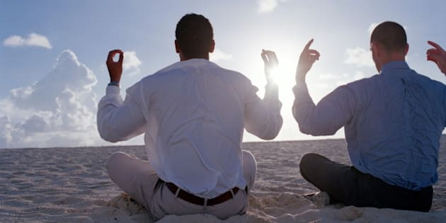 Bahamas, two businessmen meditating on beach, rear view
