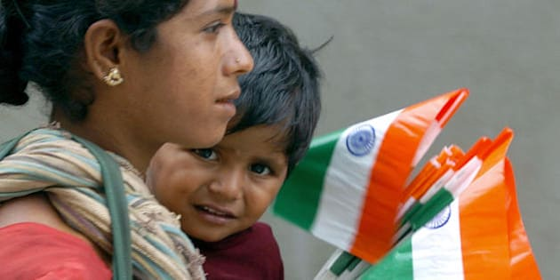 BANGALORE, INDIA:  An Indian woman carries a small child as they sell tri-colour national flags at a traffic junction in Bangalore, 14 August 2005, on the eve of the country's Independence Day celebration. India's security forces have been deployed in force across the country against possible militant attacks ahead of the 15 August celebrations marking the nation's 58th anniversary of its independence from the British rule. AFP PHOTO/Dibyangshu SARKAR,  (Photo credit should read DIBYANGSHU SARKAR/AFP/Getty Images)