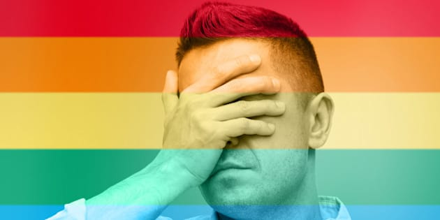 homosexual, homophobia, intolerance and people concept - unhappy gay man covering his eyes by hand over rainbow flag background