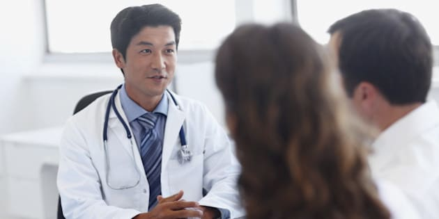 A handsome asian doctor talking with clients in his office