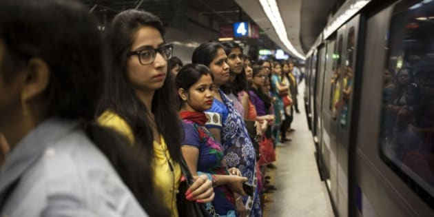 Commuters wait to board a women only compartment of a metro in New Delhi, India, Thursday, June 26, 2014. The Phase III of the Delhi metro, the Mandi House to Central Secretariat, which covers a distance of 3.2 kilometers (2 miles) opened to the public Thursday and is estimated to benefit 70,000 commuters. (AP Photo/Tsering Topgyal)